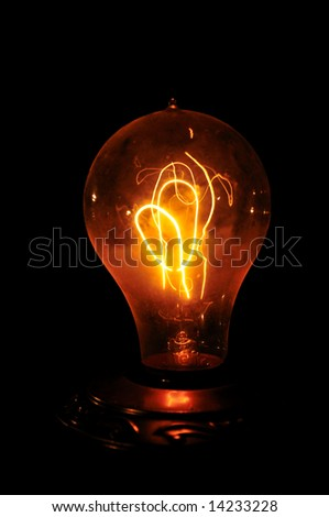 Edison light bulb with looping carbon filament. - stock photo