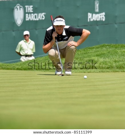 EDISON,NJ-AUGUST 24: Golfer Keegan Bradley lines up a putt during the Barclays pro-am held at the Plainfield Country Club on August 24,2011 in Edison,NJ. - stock photo