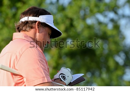 EDISON,NJ-AUGUST 24: Golfer Phil Mickelson checks his score card during the Barclays pro-am held at the Plainfield Country Club on August 24,2011 in Edison,NJ. - stock photo