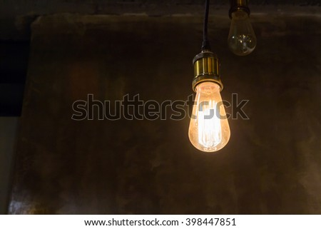 edison vintage light bulb, retro light bulb in dark room and concrete wall as background with copy space for text  concept : light decoration, idea in darkness