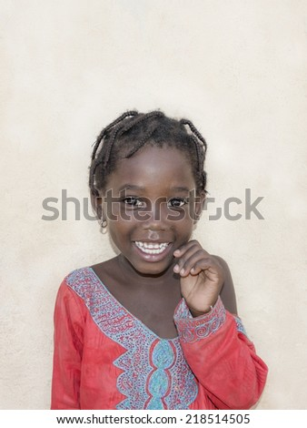 Editorial caption: THIAROYE, SENEGAL, AFRICA JULY 23, 2014 - Unidentified child in the street in front of a beige wall, popular district of Guinaw Rails - stock photo