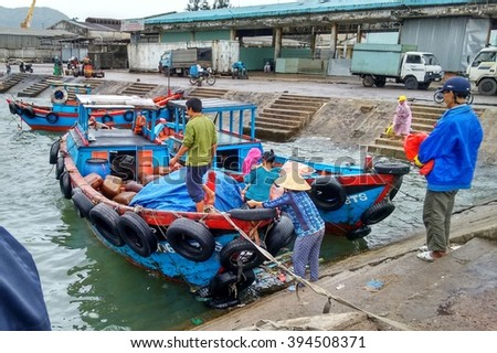 Editorial: Quy Nhon, Vietnam, 18th January 2015. Passengers boarding a small wooden boats that that brings them to a small peninsula.