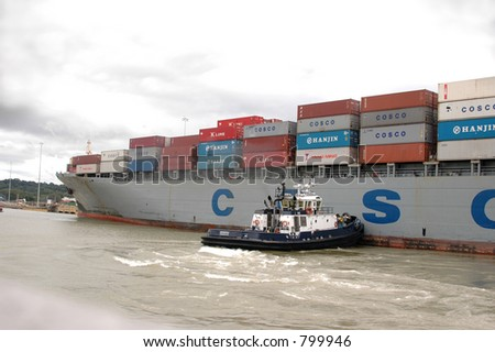 EDITORIAL tug boat guiding container ship - stock photo