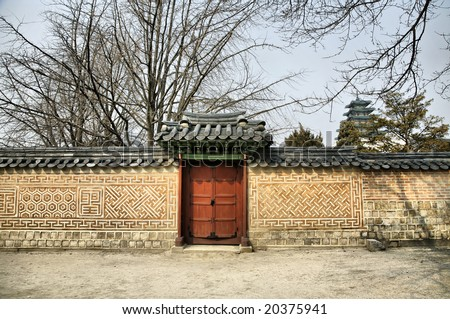 Editorial Use Only: Asian Gate along long stone wall(Release Information: Editorial Use Only. Use of this image in advertising or for promotional purposes is prohibited.) - stock photo