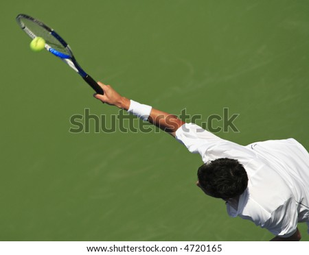 EDITORIAL USE ONLY.  Peak action shot of tennis player serving. - stock photo