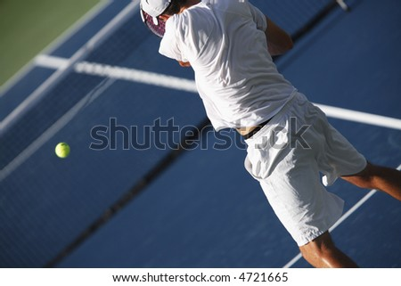 EDITORIAL USE ONLY.  Tennis player returning a serve. - stock photo