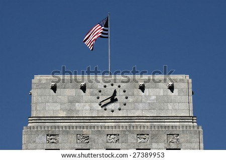 Editorial Use Only: Top of Houston City Hall with American Flag and Clock (Release Information: Editorial Use Only. Use of this image in advertising or for promotional purposes is prohibited.) - stock photo