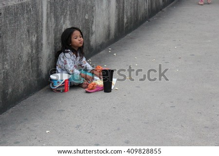 Editorial: Young Girl begging on Concrete Walkway at Motorway Interchange, Pathumthani, North Bangkok, Thailand;  19th October 2013.