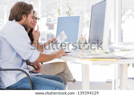 Editors going over the contact sheet at their desk in office - stock photo