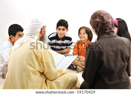 Education activity in Ramadan, Muslim arabic couple and children reading Koran - stock photo