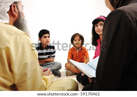 Education activity in Ramadan, Muslim couple and children reading Koran - stock photo