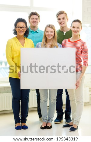 education, advertising and school concept - five smiling students with white blank board at school