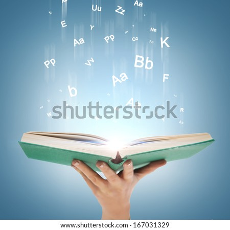 education and book concept - close up hand holding open book with magic lights - stock photo