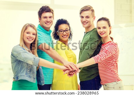 education and friendship concept - five smiling students with hands on top of each other - stock photo