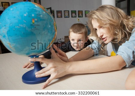 Education and fun. Globe. Kids with teacher in classroom scenery. Portrait of couple of kids in classroom, playing and educating - stock photo