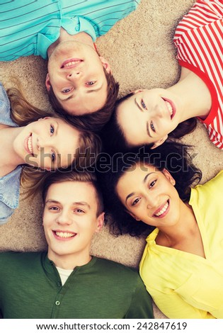 education and happiness concept - group of young smiling people lying down on floor in circle - stock photo