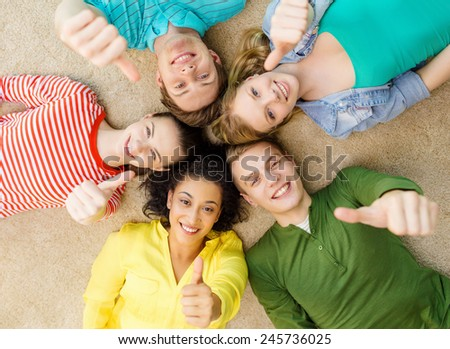 education and happiness concept - group of young smiling people lying down on floor in circle and showing thumbs up - stock photo