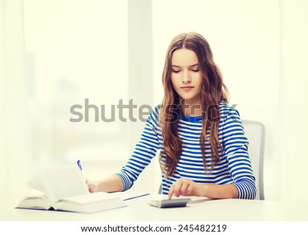 education and home concept - concecntrated student girl with notebook, calculator and book - stock photo