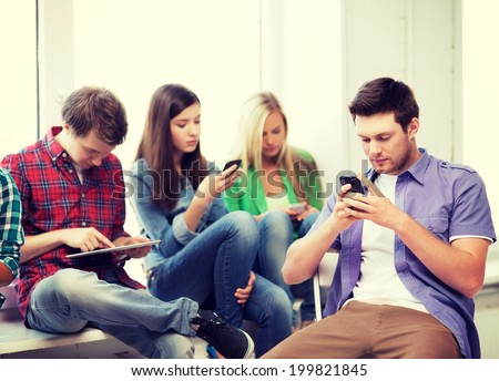 education and internet concept - students looking into phones and tablet pc - stock photo