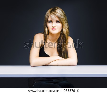 Education and learning stock image of university student sitting at classroom desk with space for text to left and copyspace to right, on dark background - stock photo