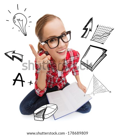 education and leisure concept - smiling teenage girl in black eyeglasses reading book - stock photo