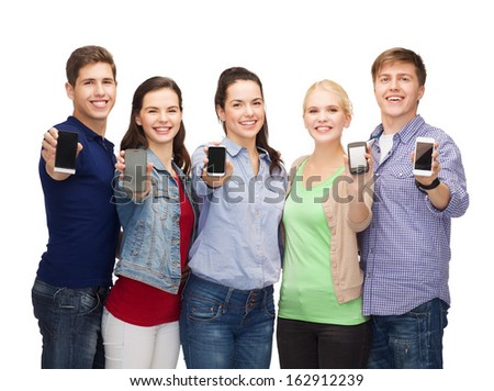 education and modern technology concept - smiling students showing blank smartphones screens