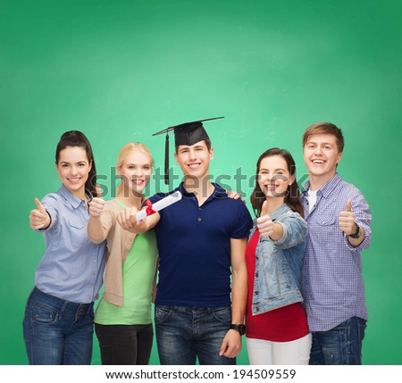 education and people concept - group of standing smiling students with diploma and corner-cap showing thumbs up - stock photo