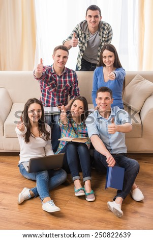 Education and people concept. Group of students are sitting on sofa and on the floor with laptop and books are showing thumbs up. - stock photo