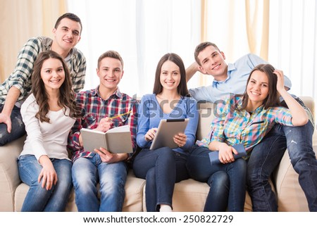 Education and people concept. Group of students are sitting on the sofa, with tablet and book are looking at the camera. - stock photo