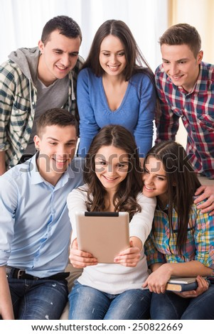 Education and people concept. Group of students with tablet are making selfie photo. - stock photo