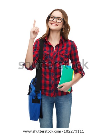 education and people concept - smiling female student in eyeglasses with bag and notebooks showing direction - stock photo