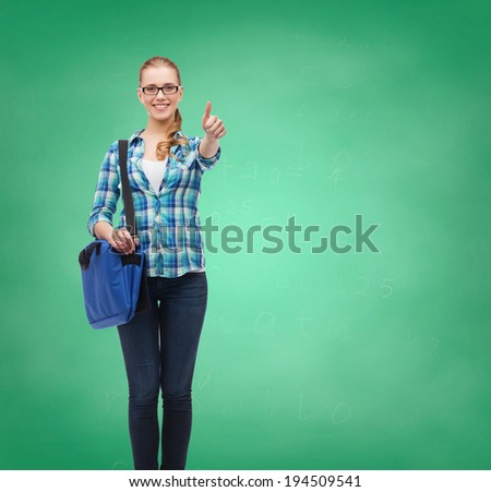 education and people concept - smiling female student in eyeglasses with laptop bag showing thumbs up on green board background - stock photo