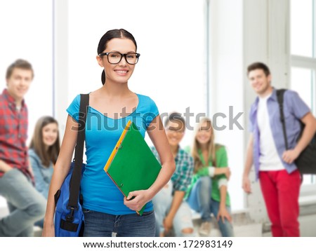 education and people concept - smiling student in eyeglasses with bag and folders standing - stock photo