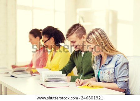 education and school concept - five smiling students with textbooks and books at school