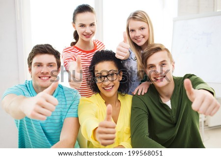 education and school concept - group of smiling students at school showing thumbs up