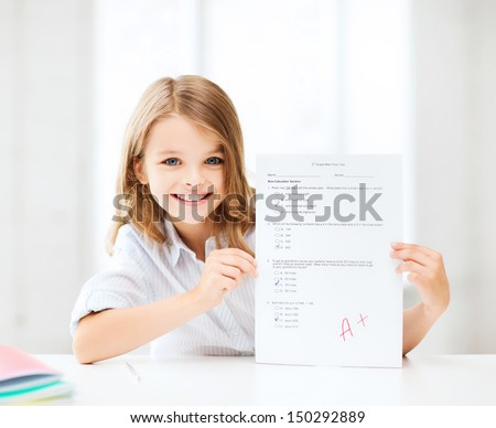 education and school concept - little school girl with test and A grade at school - stock photo
