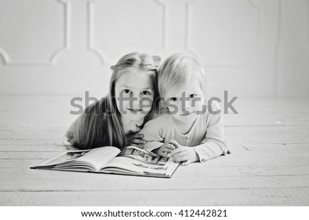 education and school concept - little sisters lying on a floor with a book studying and reading. happy kids boys brothers reading encyclopedia together at home - black and white - stock photo