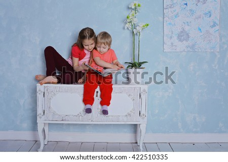 education and school concept - little sisters sitting with a book studying and reading. happy kids reading encyclopedia together at home - stock photo