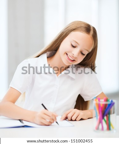 education and school concept - little student girl drawing at school - stock photo