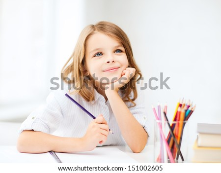 education and school concept - little student girl drawing with pencils at school - stock photo