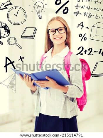 education and school concept - little student girl reading book at school - stock photo