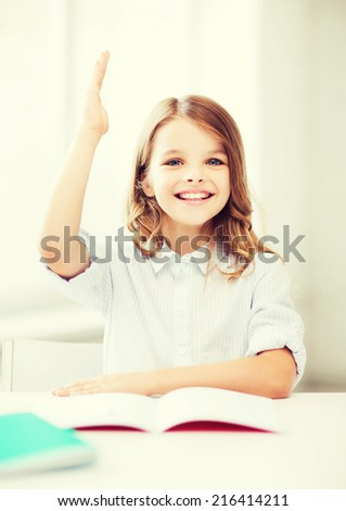 education and school concept - little student girl studying and raising hand at school - stock photo