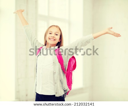 education and school concept - little student girl with hands up at school