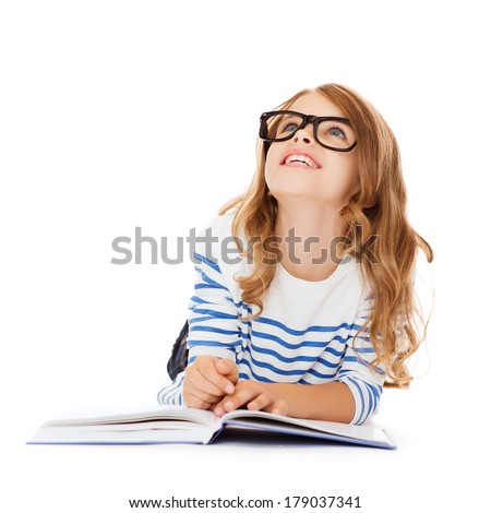 education and school concept - smiling little student girl with book and eyeglasses lying on the floor and looking up - stock photo