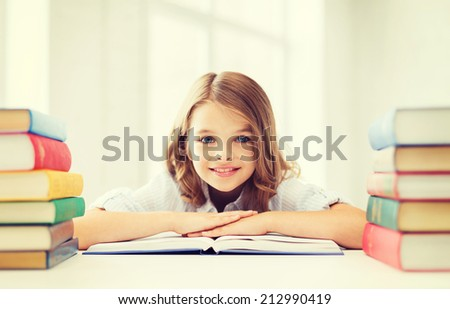 education and school concept - smiling little student girl with many books at school