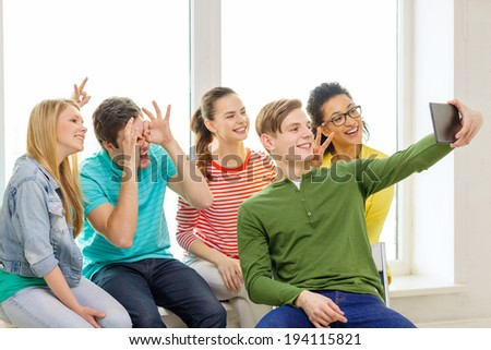 education and technology concept - smiling students taking selfie with tablet pc computer at school