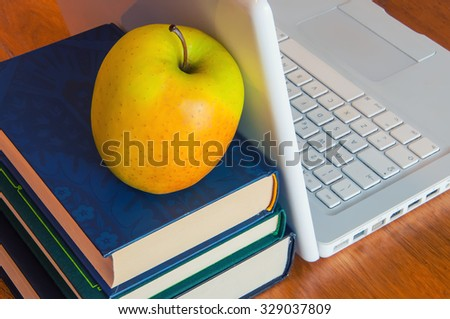 Education and technology concept with laptop and books - stock photo