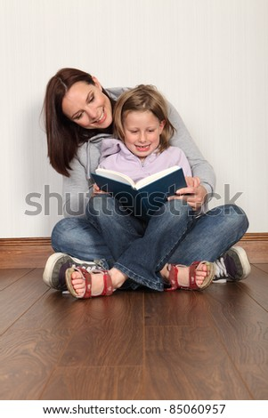Education at home for young primary school girl with mother teaching her to read a book. Both wearing denim jeans and hoodies sitting cross legged on the floor. - stock photo