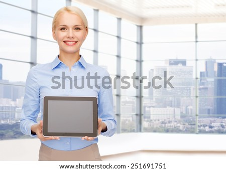 education, business and technology concept - smiling businesswoman or student showing tablet pc computer blank screen over office room or new apartment background