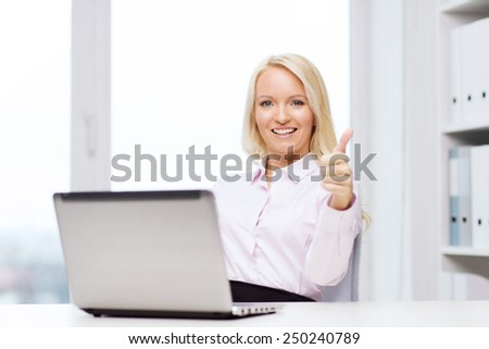 education, business and technology concept - smiling businesswoman or student showing thumbs up with laptop computer in office - stock photo